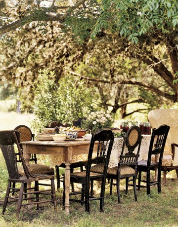 Alfresco dining at a rustic table with mismatched chairs.