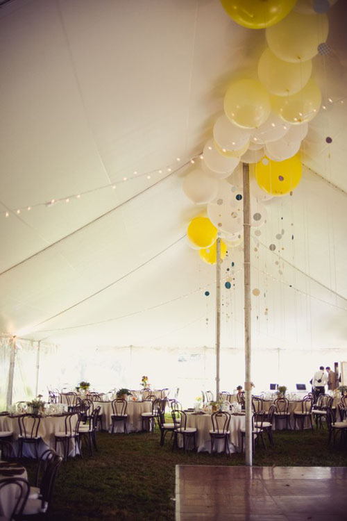 Yellow and white balloons in the top peak of a tent for a wedding reception