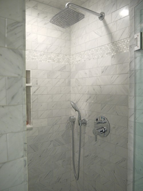 Marble subway tile shower with marble mosaics inset