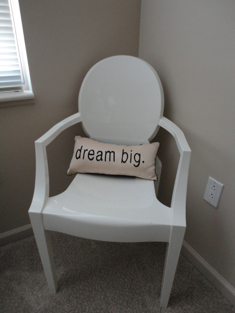 Louis Ghost chair in white with a dream big pillow resting on it in the corner of a bedroom