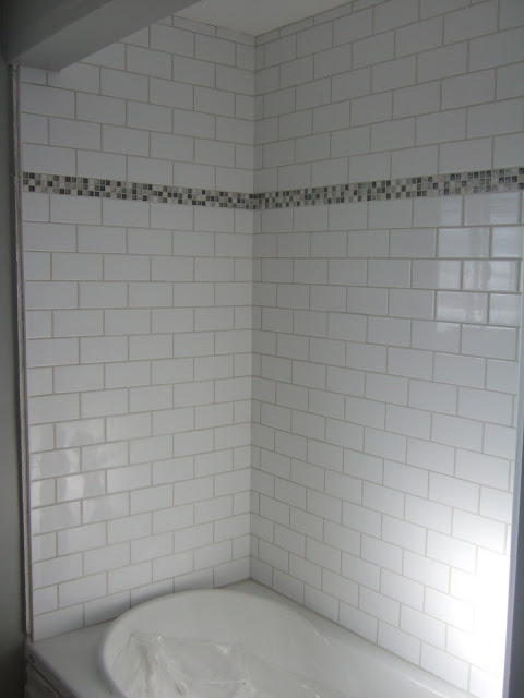 Subway tile shower with inset of small gray mosaics