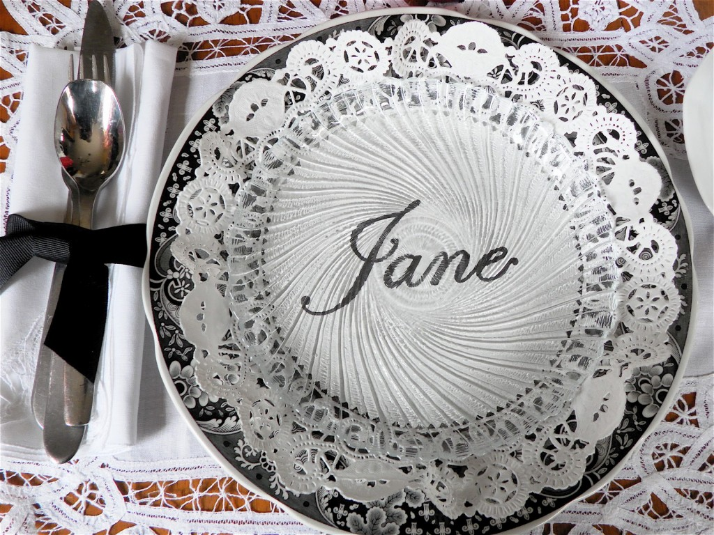 Doily place card set under a clear plate