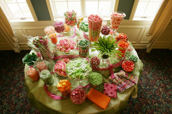 Wedding candy buffet with orange, pink and lime green candies.