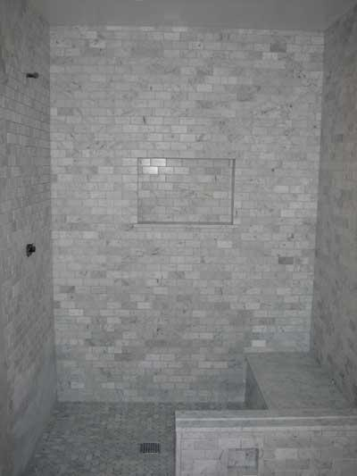 Marble mosaic tile shower with niche for shampoo and built in bench