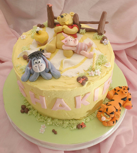 Winnie the Pooh, tigger, piglet and Eeyore resting on a birthday cake