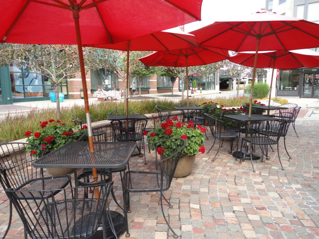 Cafe tables with umbrellas everywhere for residents and guests to enjoy and use