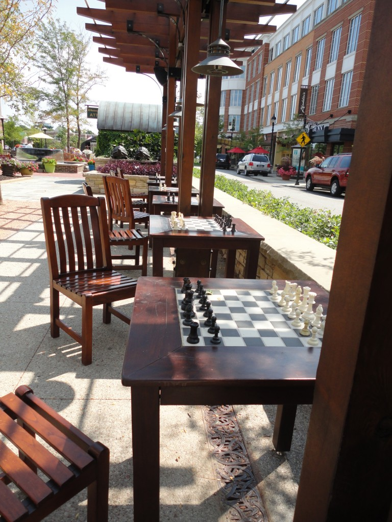 Row of chessboards set up ready for people to play in the park