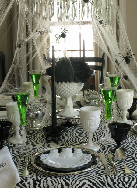 Black and white Halloween table setting with a punch of color from the green potions served in the champagne flutes.