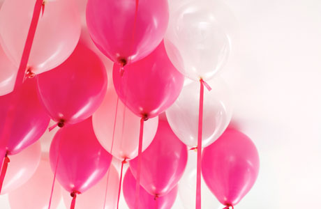 Pink and white balloons tied with contrasting ribbons and floated