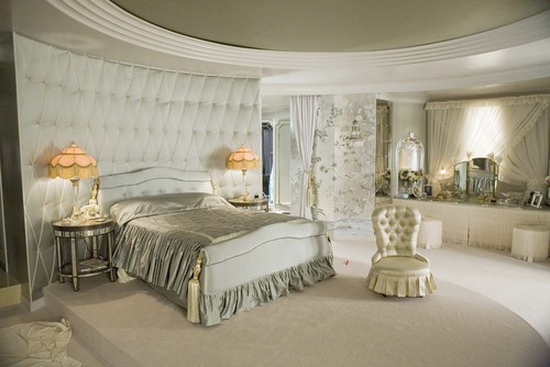 Glamourous bedroom with upholstered walls and victorian lamps