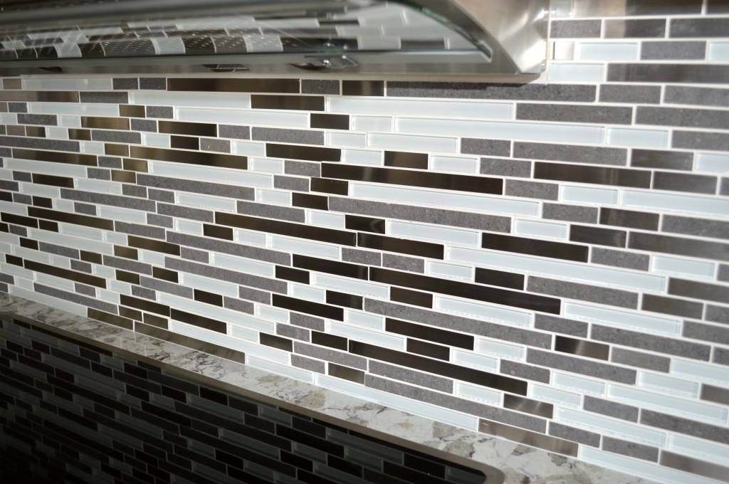 Gray, white, stainless and glass tile backsplash