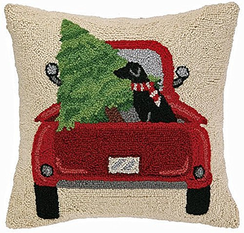 Christmas pillow with a red pick up truck with a Christmas tree and a black lab in the back