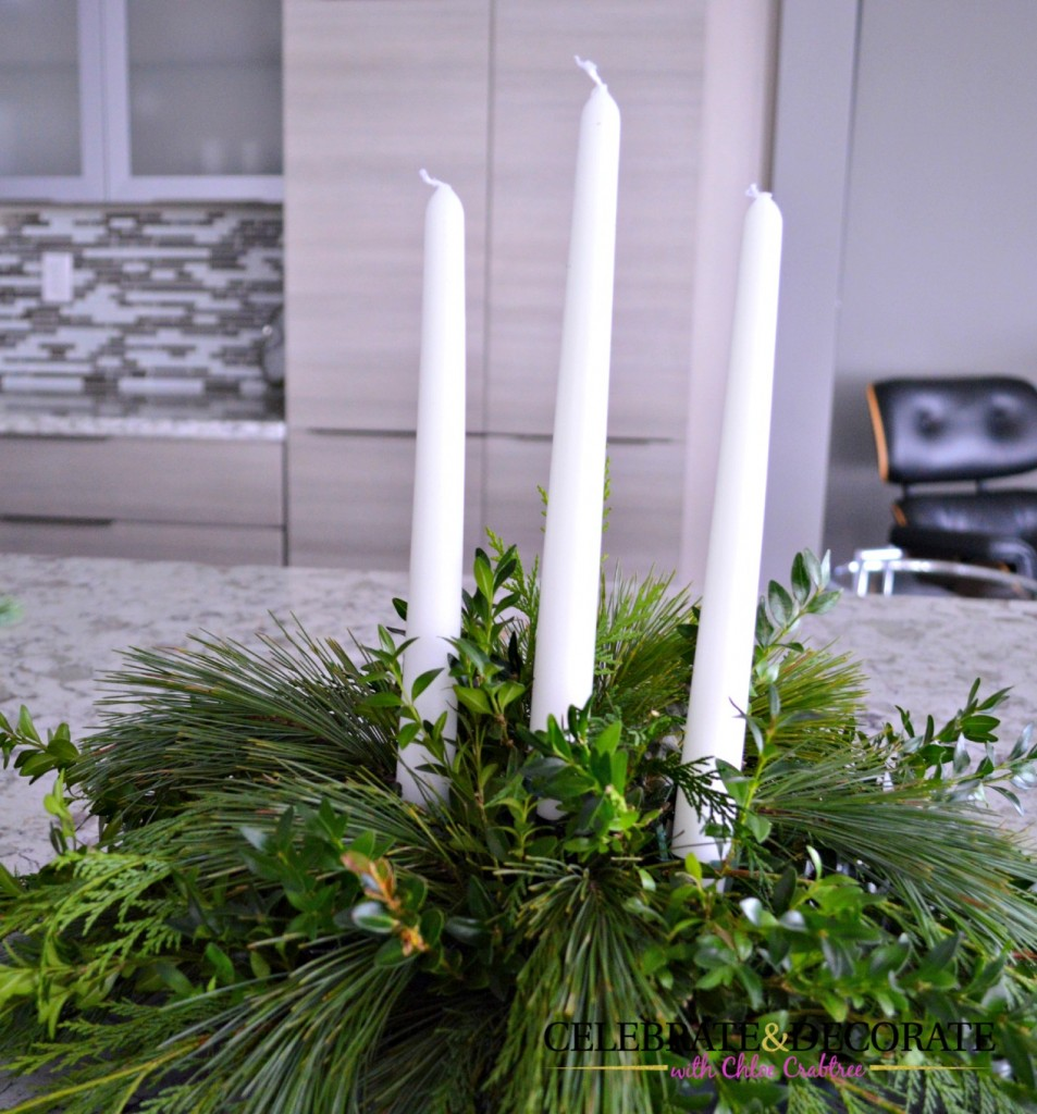 Three candles in an evergreen centerpiece