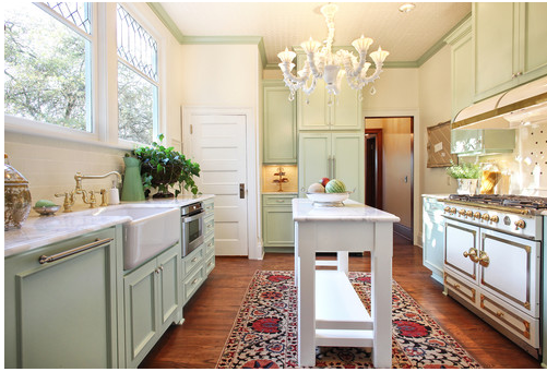 Pale painted cabinets with a farmhouse sink and a narrow island.