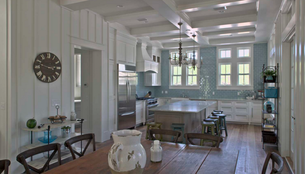 Crisp White Farmhouse kitchen with blue tile backsplash up the window wall.