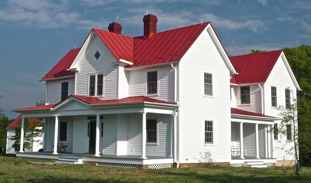 Classic white farmhouse with a red metal roof. - Celebrate & Decorate