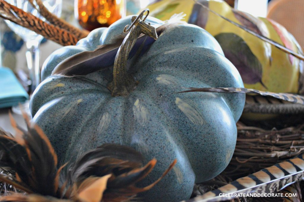A blue pumpkin and pheasant feathers whisper that Fall is coming. They will be decorating a Fall table.