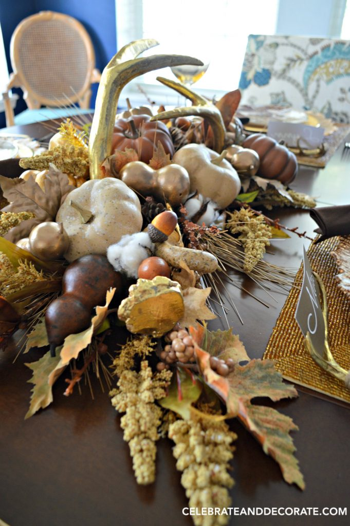A Fall Tablescape centerpiece for Thanksgiving dinner featuring golden antlers, cotton bolls, acorns, leaves and gourds in shades of gold, cream and brown.