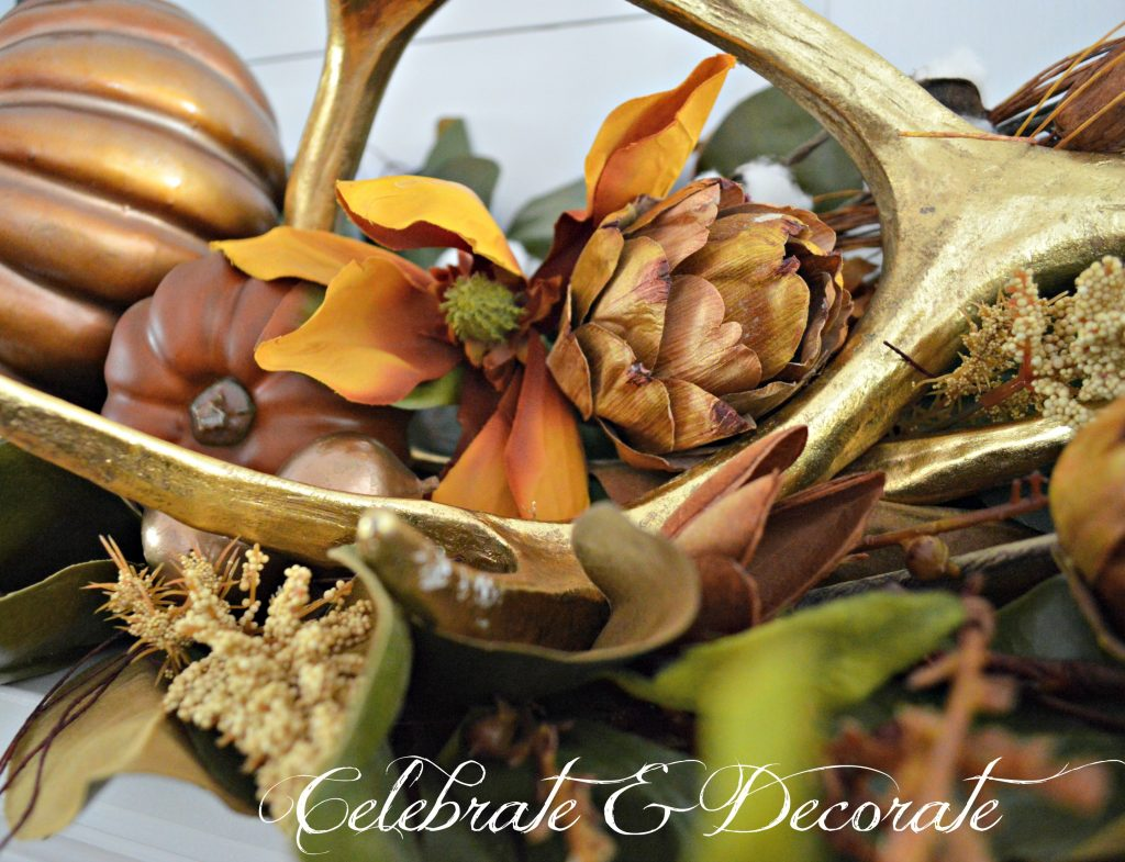 Dried magnolia blossoms and dried artichokes are nestled amongst the antlers and magnolias on this Fall mantel.