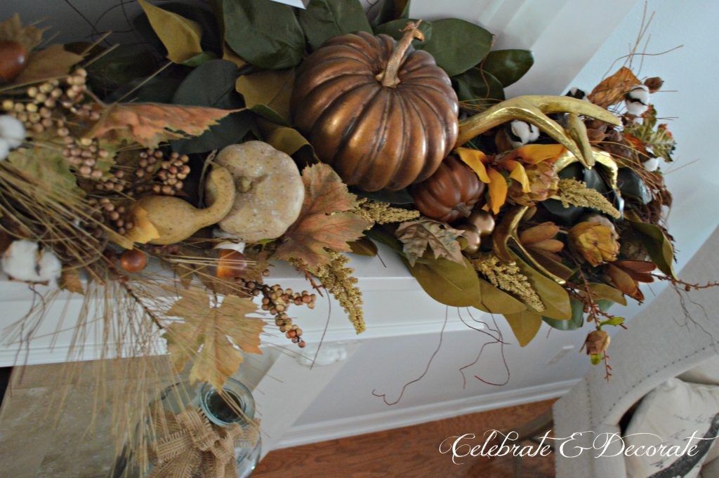 Magnolias, cotton bolls, gourds, pumpkins and antlers make for a lavish display on this Fall or Thanksgiving mantel.