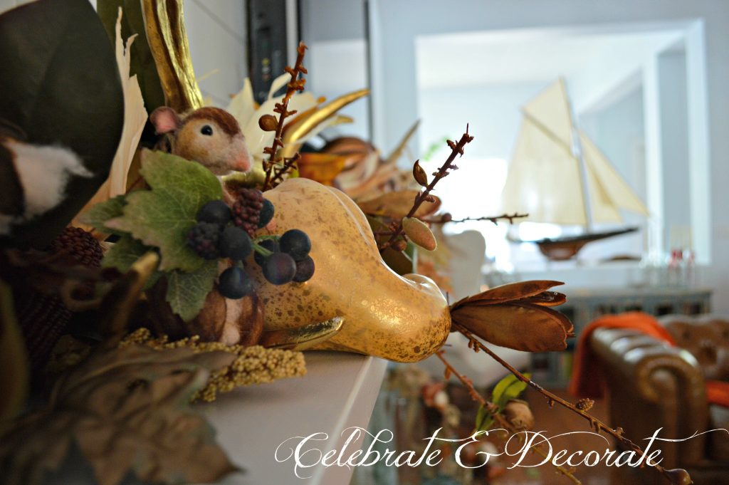 A tiny needled felted mouse peeks out among from the display on this stunning Fall mantel.