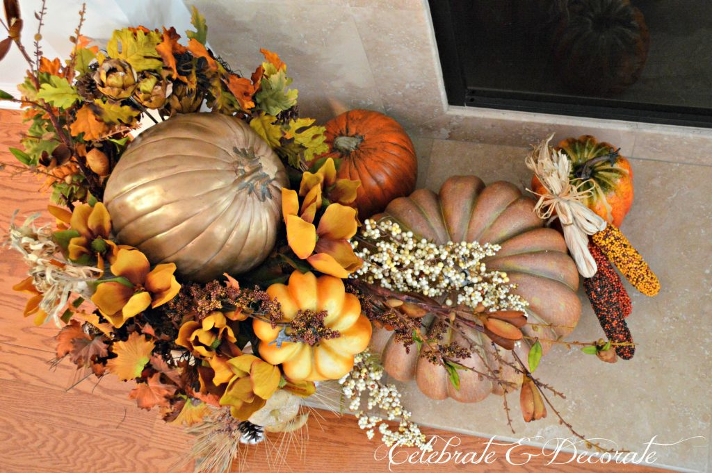 A splendid arrangement of leaves and pumpkins grace the hearth in this Thanksgiving display.