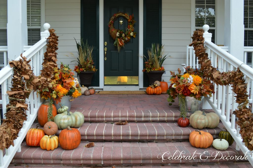 A lush front porch all decked out for Fall with Fall florals and pumpkins