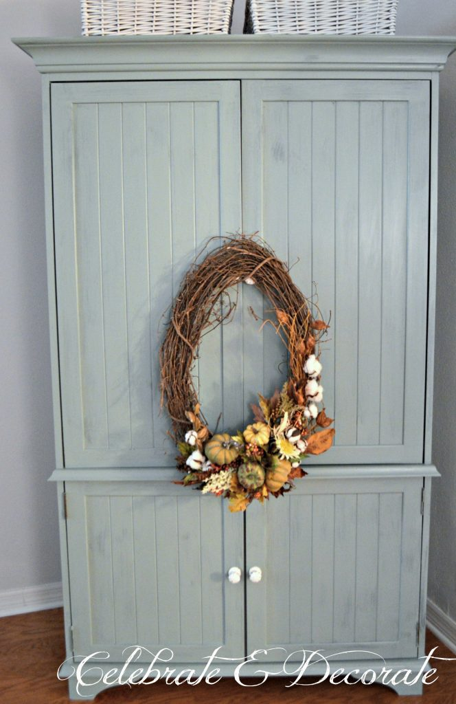 A pale blue milk paint armoire supports a pretty oval Fall wreath for a touch of Autumn decor in the bedroom.