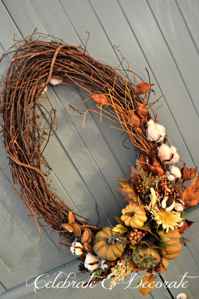 An oval grapevine wreath is decorated with cotton bolls, Fall leaves and pumpkins.
