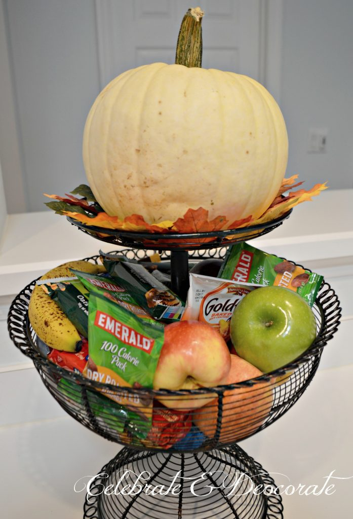 A White pumpkin adorns a tiered basket of snacks in the kitchen at this Fall Home Tour