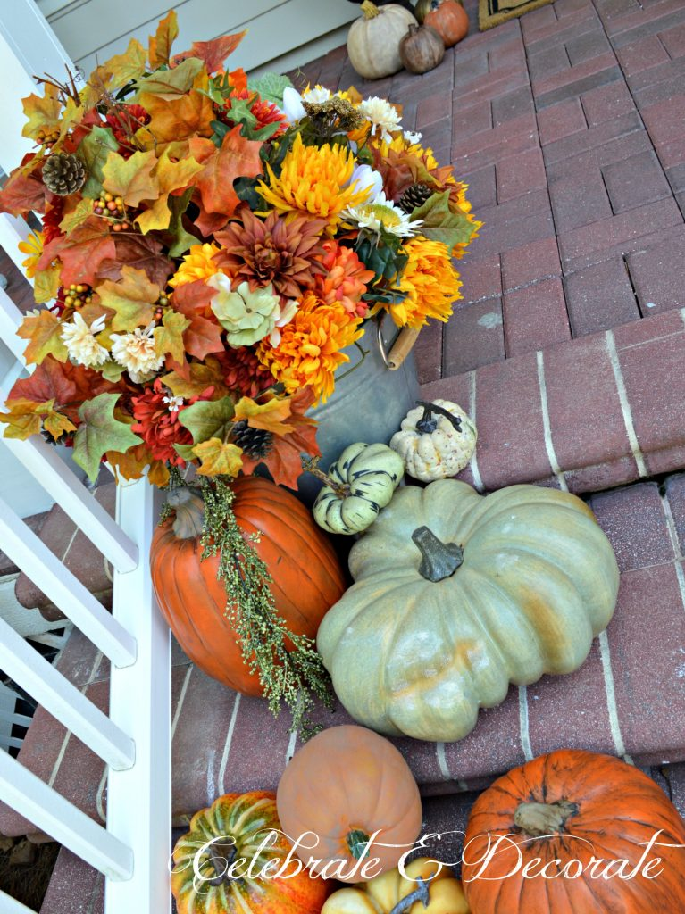 For a farmhouse feel to your front porch fill galvanized tubs or bushel baskets with faux fall flowers
