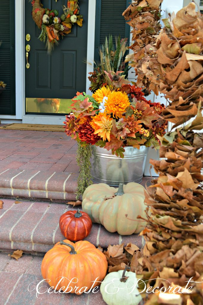 Galvanized tubs of faux fall flowers and leaves add to the farmhouse feel of this Fall front porch