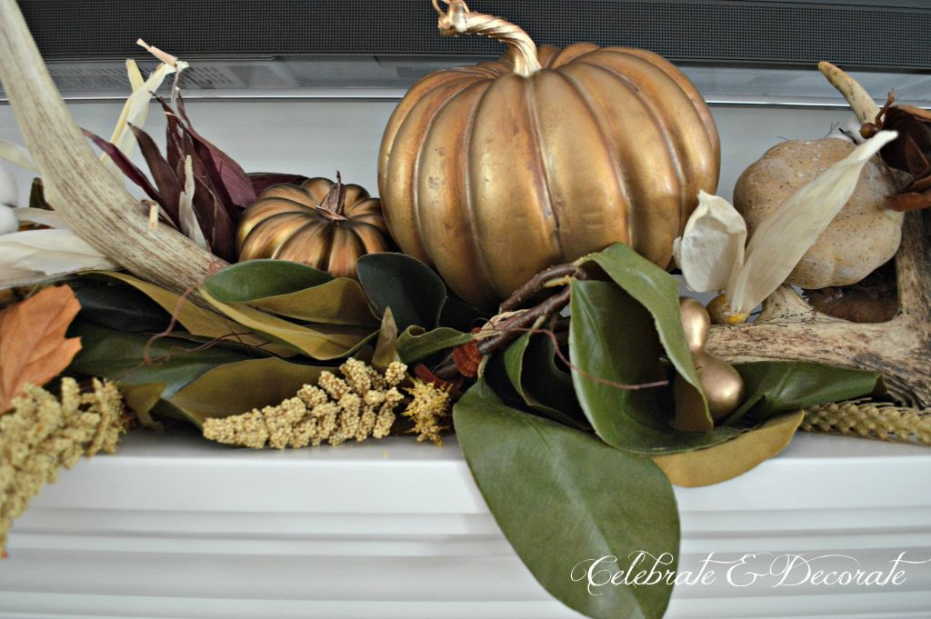 Gilded pumpkins dress the mantel nestled among antlers on this stunning Fall display.