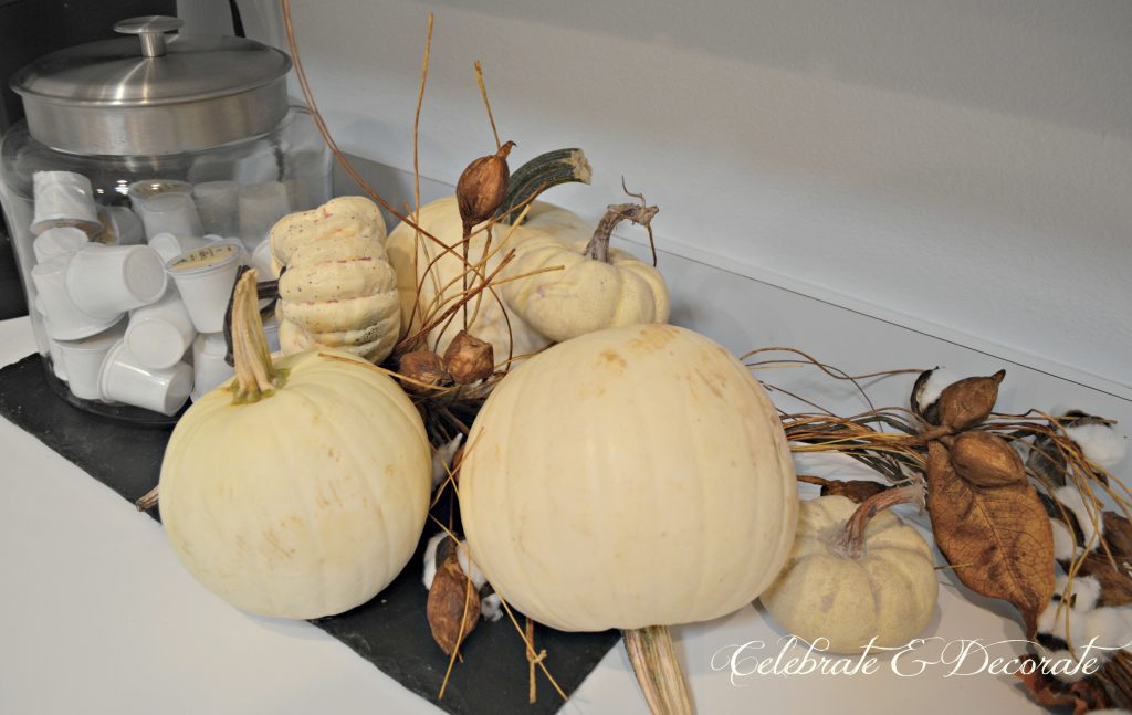 White pumpkins and cotton boll garlands tumble along the kitchen counter atop a slate board.