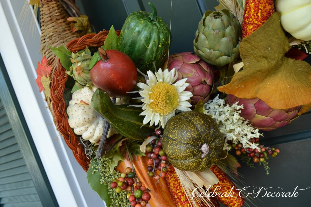 A cornucopia adorns this Fall wreath with the fruits of the harvest tumbling out of the cornucopia and flowing around the grapevine wreath.