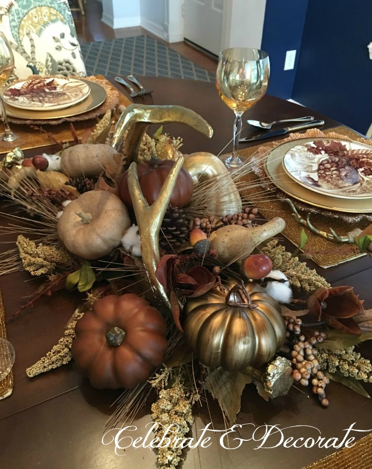 Golden Fall tablescape with a centerpiece of pumpkins and golden antlers.