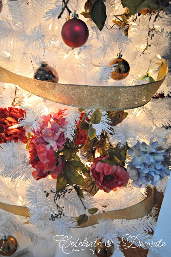 A White Christmas tree decorated with garlands of jewel tone flowers.