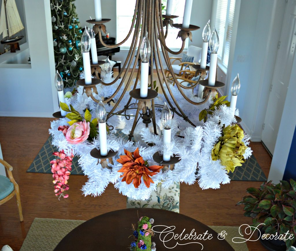 White Garland on a chandelier to match the white Christmas tree.