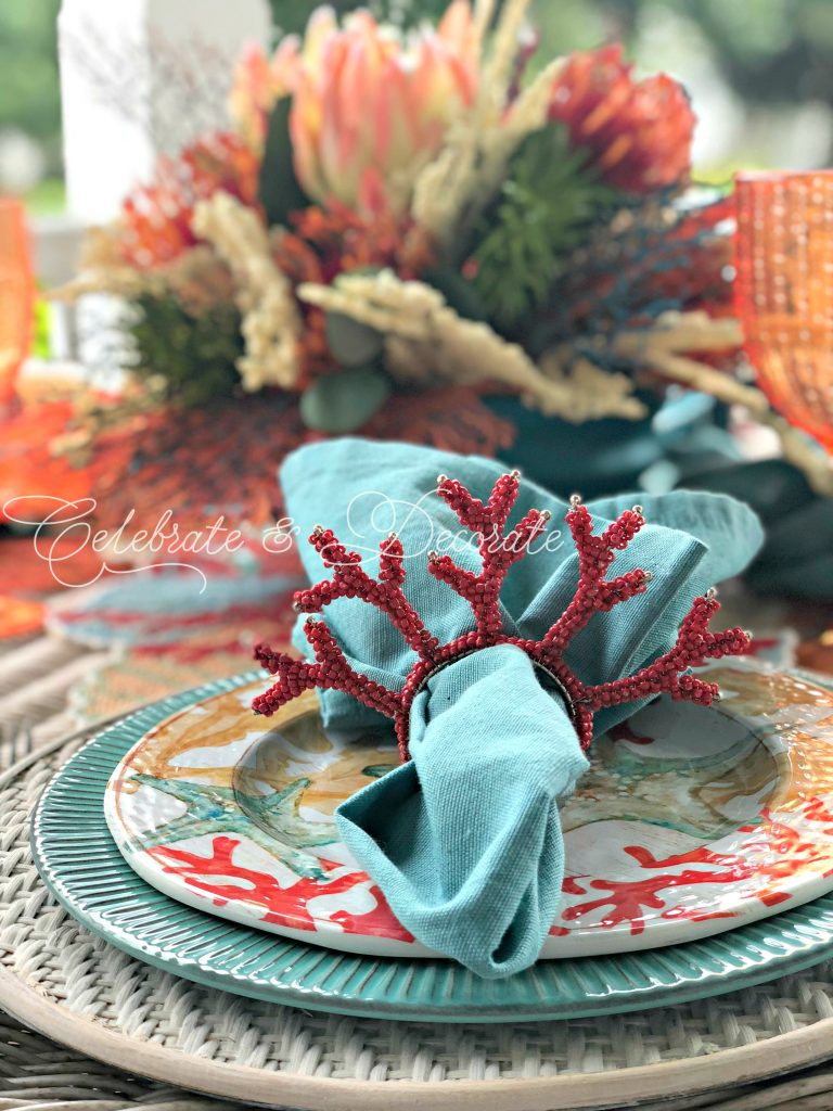 Beaded coral napkin rings help set the mood for a coastal dinner table.