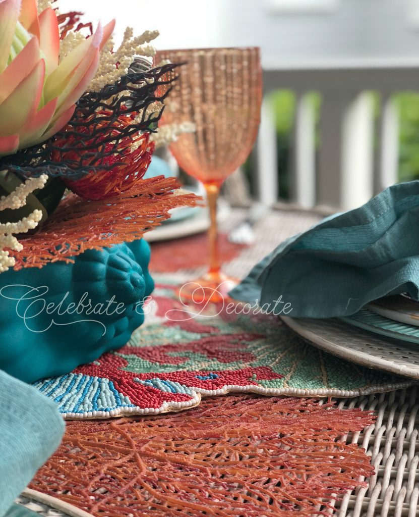 Setting a coral coastal tablescape.