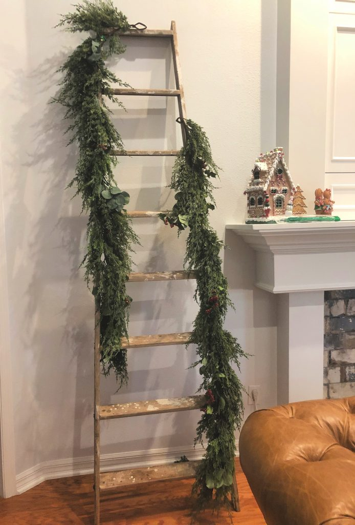 I had a couple of artificial garlands so I began with those, attaching one to the top of the ladder on one side. I simply used pipe cleaners to secure it.