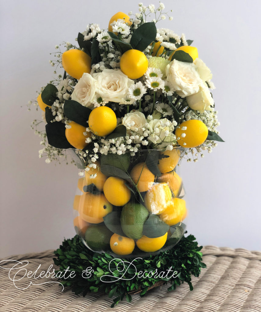 A centerpiece of lemons and limes in a glass vase with white flowers
