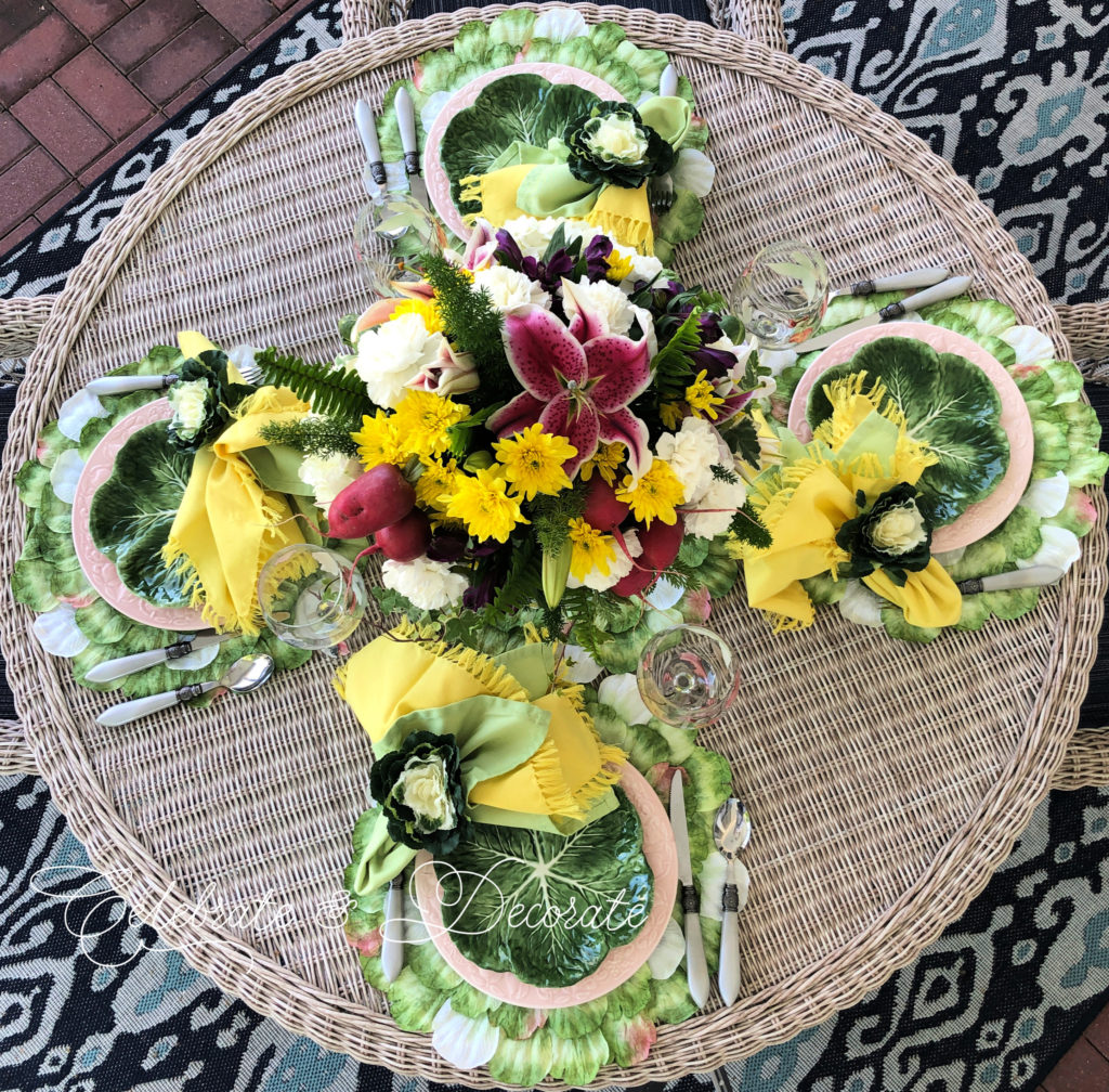 Floral centerpiece on table top with cabbage plates.