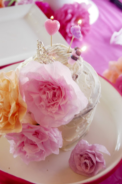 Little cake with pink paper flower decorations.