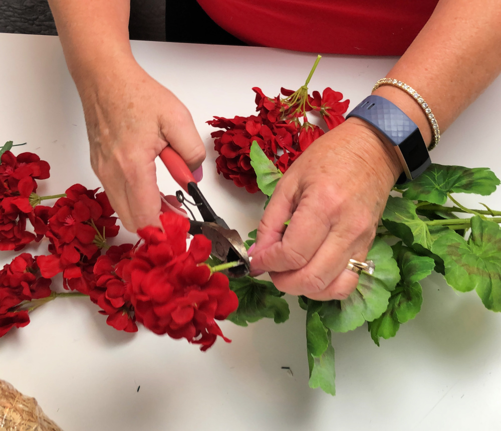 Using wire cutters to cut apart an artificial red geranium bush.