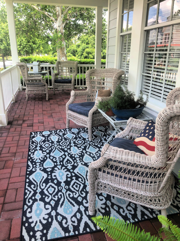 Front porch with comfy oversized chairs and shades of blue indoor/outdoor rugs