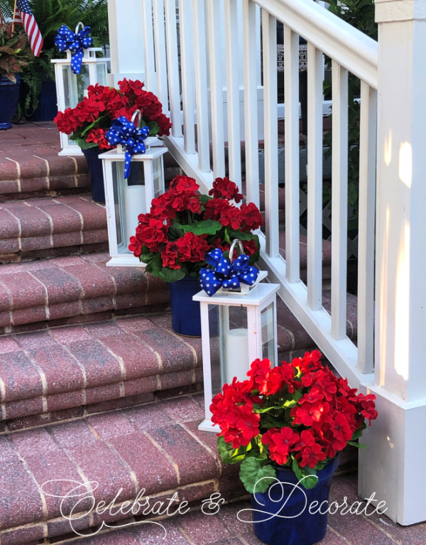 White lanterns and red geraniums decorate brick steps