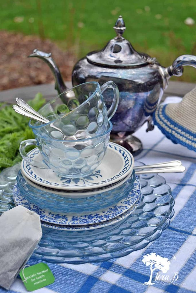 Stack of pretty blue plates and a silver tea pot.