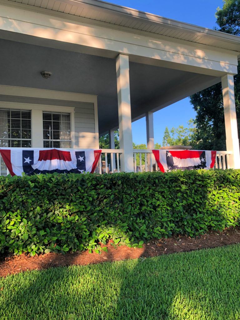 Red white and blue banners decorate a wrap around porch