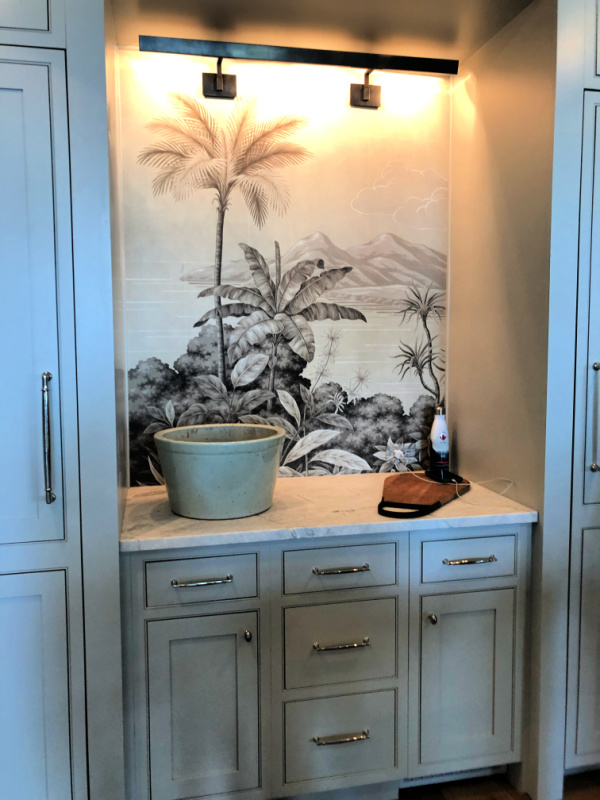 Kitchen counter with palm wallpaper behind it